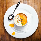 Pumpkin soup with cream and pumpkin seeds in a white bowl on woo Royalty Free Stock Images