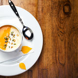 Pumpkin soup with cream and pumpkin seeds in a white bowl on woo Royalty Free Stock Photography