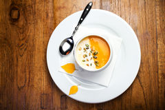 Pumpkin soup with cream and pumpkin seeds in a white bowl on woo Stock Photos