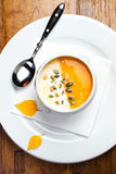 Pumpkin soup with cream and pumpkin seeds in a white bowl on woo Royalty Free Stock Photo