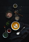Pumpkin soup with cream, seedsand various spicesl in rustic metal bowl over grunge black background. Top view. Stock Photography