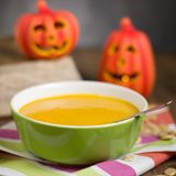Pumpkin soup. Creamy plain pumpkin soup in green dish. Decorated by halloween jack-o-lanterns and some pumpkin seeds Royalty Free Stock Photo