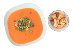 Pumpkin soup with croutons. Pumpkin soup with pumpkin seeds and parsley. Soup served with croutons, completely isolated on white background royalty free stock photography
