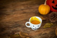Pumpkin soup in a cup with Halloween anthropomorphic smiley face. Autumn season comfort food. Pumpkin soup in a cup with Halloween anthropomorphic smiley face stock photography
