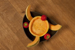 Pumpkin soup. Pumpkin soup in a pumpkin decorated with strawberries Royalty Free Stock Photography