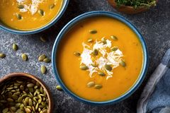 Pumpkin Soup. Delicious creamy homemade pumpkin soup with cream and pumpkin seed garnish stock photo