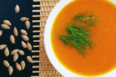 Pumpkin soup with dill and bread on a mat and pumpkin seeds Stock Image