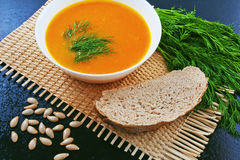 Pumpkin soup with dill and bread on a mat and pumpkin seeds Stock Photo