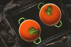 Pumpkin soup in green small pots on a black wooden background with wooden spoons and a napkin. View from above. Stock Photo