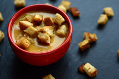 Pumpkin soup with homemade croutons in a small, red bowl Stock Photography