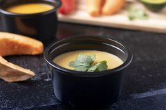 Pumpkin soup and mint leaves, spoon, pepper and pea porridge in food container on wooden table, blurred bacground stock image