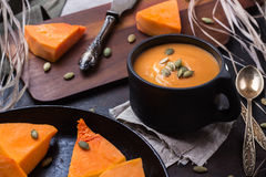 Pumpkin soup in a mug on grunge black table Royalty Free Stock Images
