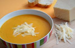 Pumpkin soup with parmesan cheese and baguettes. Creamy pumpkin soup served with parmesan cheese and baguettes Stock Photo
