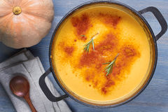 Pumpkin soup in pot on wooden table Stock Image