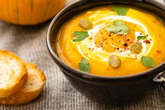 Pumpkin soup with pumpkin seeds on a bowl on linen textile background, top view. Autumn concept. stock image