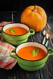 Pumpkin soup puree in ceramic small green saucepans on a wooden table. Pumpkin soup puree in ceramic small green saucepans on a wooden table Royalty Free Stock Images
