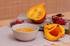 Pumpkin Soup and Rowanberries. Autumn Still Life: bowl of delicious pumpkin soup. Sliced pumpkin and rowanberries royalty free stock images