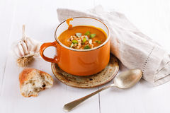 Pumpkin soup with rustic bread and garlic. Bowl of creamy pumpkin soup with rustic bread and garlic on a white background. Selective focus royalty free stock images