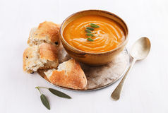 Pumpkin soup with rustic bread on white background. Bowl of creamy pumpkin soup with sage leaves and rustic bread on a silver tray on a wooden white background Royalty Free Stock Images