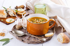 Pumpkin soup with rustic bread on white background. Bowl of creamy pumpkin soup with thyme and sage leaves, rustic bread and garlic on a woven plate on a white royalty free stock photos