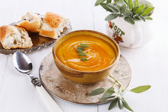Pumpkin soup with sage on white background. Bowl of creamy pumpkin soup with sage leaves and rustic bread on a silver plate on a white background. Selective stock images