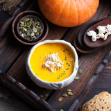 Pumpkin soup with salty popcorn in a white ceramic bowl with fresh pumpkin Top view Royalty Free Stock Images