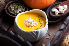 Pumpkin soup with salty popcorn in a white ceramic bowl with fresh pumpkin on a wooden background Royalty Free Stock Images