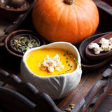 Pumpkin soup with salty popcorn in a white ceramic bowl with fresh pumpkin on a wooden background Stock Image