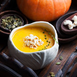 Pumpkin soup with salty popcorn in a white ceramic bowl with fresh pumpkin on a wooden background Royalty Free Stock Photo