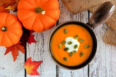 Pumpkin soup, scene on rustic wood background with autumn leaves Royalty Free Stock Images