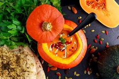 Pumpkin soup with seeds, goji berries, parsley and garlic flat bread for autumn dinner Royalty Free Stock Images