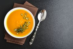 Pumpkin soup with seeds. And spoon on grunge black slate background, top view Royalty Free Stock Images