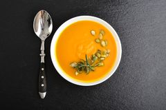 Pumpkin soup with seeds. And spoon on grunge black slate background, top view Royalty Free Stock Photo