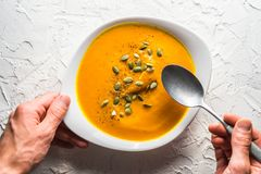 Pumpkin soup with seeds and a spoon in hand Stock Photo