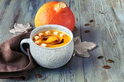 Pumpkin soup  served in blue ceramic cup with croutons and pumpk. In oil on light blue rustic table, text space Stock Image