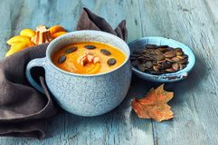 Pumpkin soup  served in blue ceramic cup with croutons and pumpk. In seeds on light blue rustic table, text space Royalty Free Stock Photo
