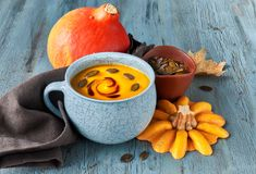Pumpkin soup served in blue ceramic cup with pumpkin seeds and o. Il on light blue rustic table Royalty Free Stock Images