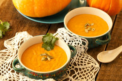 Pumpkin soup served in a ceramic plate, decorated with pumpkin s Stock Photos