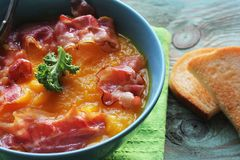 Pumpkin soup served with crispy bacon. Top view stock photos