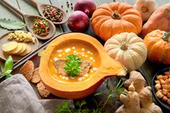 Pumpkin soup served in a hollowed pumpkin with croutons, parsley. And cream, with ingredients around. Autumn food background Stock Photography