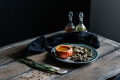 Pumpkin soup served in pumpkin, and mushroom on plate- dark and moody Royalty Free Stock Images