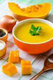 The pumpkin soup served on the table in bowl. Pumpkin soup served on the table in bowl Stock Photos