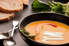 Pumpkin soup with shrimp, sour in dark bowl and bread near silver spoons, greenery stock photography