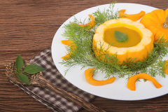 Pumpkin soup in a small pumpkin with herb leaf Stock Images