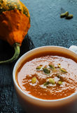 Pumpkin soup in a small white bowl and a pumpkin. On the stone black background Stock Photo