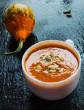 Pumpkin soup in a small white bowl and a pumpkin. On the stone black background Royalty Free Stock Images