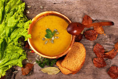 Pumpkin soup with spoon bread and salad leaves royalty free stock photos