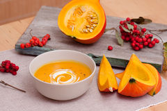 Pumpkin soup. With swirl of fresh cream with half pumpkin and rowan berries on a wooden board royalty free stock image