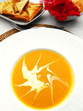 Pumpkin soup. And toasts - a photograph showing a dish of orange  potage with whipped cream forming a star shape pattern on it, served with hot golden brown Royalty Free Stock Photos