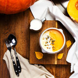 Pumpkin Soup with whipped cream and pumpkin seeds in a white pla Royalty Free Stock Photos